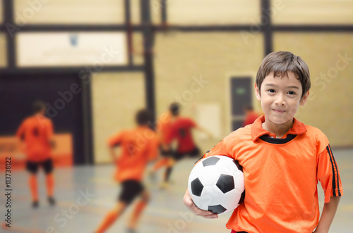 Little boy holding football in futsal gym