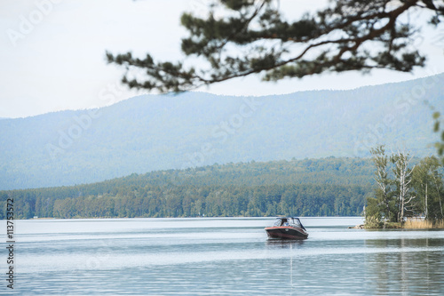 motor boat floats on water of lake surrounded by mountains and forests
