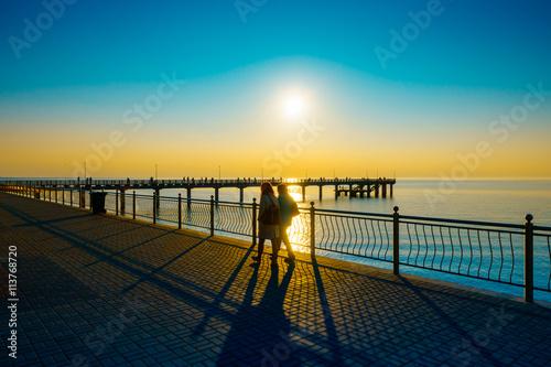 fototapeta na lodówkę People walking on the embankment at Baltic Sea coast