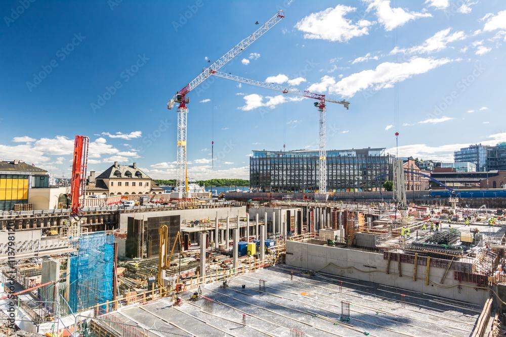 Fototapeta Großbaustelle mit Betonfundament und Kränen im Hintergrund