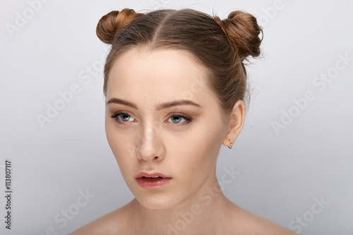 plakat Portrait of a young woman with funny hairstyle and bare shoulders act the ape against white studio background