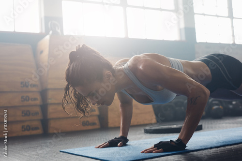 Photo  Young woman doing push-ups at the gym
