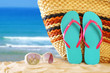 tropical sandy beach, straw bag, sunglasses and and flip flops