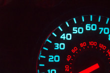 Part Of A Blue And Red Speedometer At Night