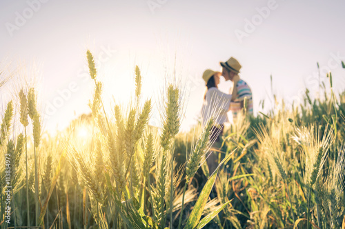 Valokuva  Couple of lovers kissing in a wheat field