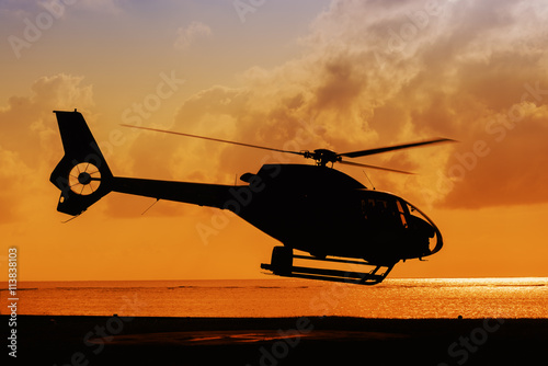 Fotobehang Helicopter silhouette of helicopter taking off at sunset