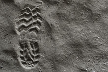 Close Up Bott Or Shoe Print, Left Foot With Grip Set Deeply Into Dirty Sand, Left Side. Hdr Picture.
