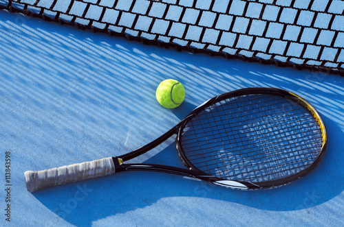 Tennis racket and ball on blue tarmac, net casting shadow Wallpaper Mural