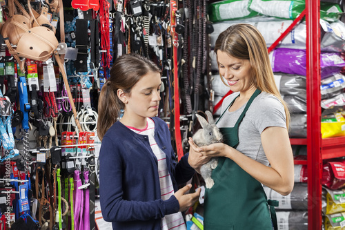 Poster Amusementspark Saleswoman Holding Rabbit With Girl At Pet Store