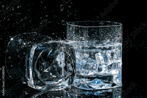 Photo  Two high quality glasses of whiskey, one lies on side and other with ice cubes and water splashes