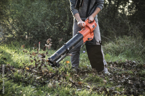Worker on a garden in autumn with a leaf blower Canvas Print