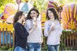 Beautiful young women smiling eating ice-cream and talking in th