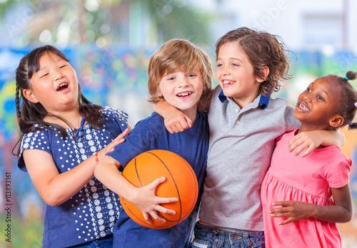 Plakat Szczęśliwi dzieci obejmuje podczas gdy bawić się koszykówkę. Primary schoo