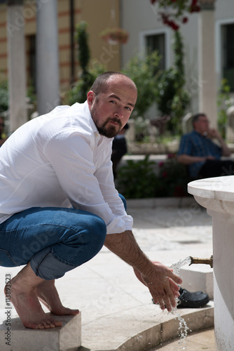 Fotografia, Obraz  man preparing for ablution