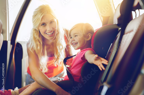Vászonkép happy mother fastening child with car seat belt