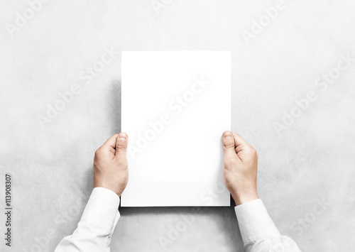 Fotografering  Hand holding white blank paper sheet mockup, isolated