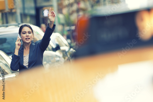 Photo New York City Woman on Cell Phone Hailing a Yellow Taxi Cab