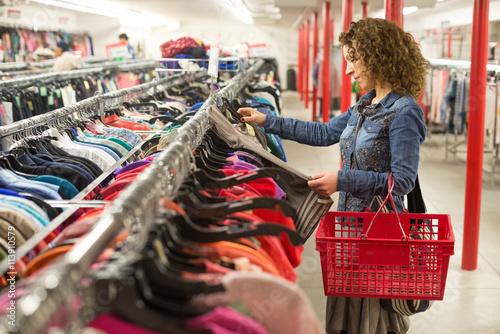 Zdjęcie XXL Kobieta przeglądając ubrania w sklepie z artykułami używanymi