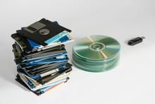 Pile Of Floppy Disks, Cd-roms, External Hard Drive And Pen Over White