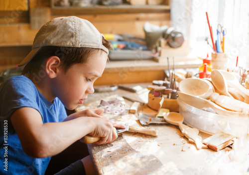 Valokuva  boy learning wood carving. young carpenter working in a workshop