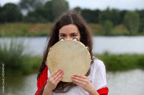 Stampa su Tela Young brunette woman hiding her face behind a tambourine