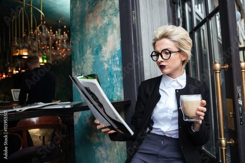 Photographie  Close-up portrait d'une jeune fille assise dans le café avec le magazine