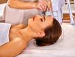 young woman receiving electroporation facial massage at massage salon.