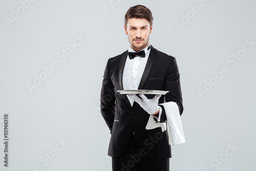 Fotografie, Obraz  Handsome yong waiter in tuxedo and gloves holding empty tray