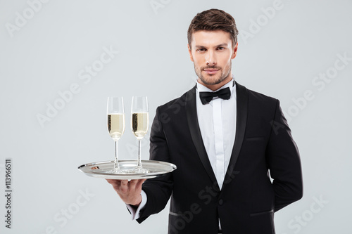 Fotografía  Butler in tuxedo holding tray with two glasses of champagne