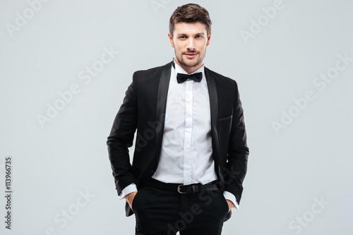 Obraz na płótnie Confident young man in tuxedo with bowtie