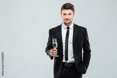 fototapeta na ścianę Confident man in suit and tie holding glass of champagne