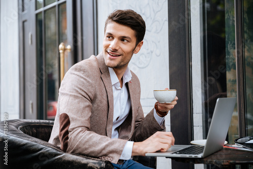 Láminas  Businessman holding cup of coffee and working with laptop outdoors