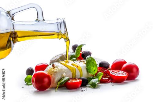 Fototapeta Caprese. Caprese salad. Italian salad. Mediterranean salad. Italian cuisine. Mediterranean cuisine. Tomato mozzarella basil leaves black olives and olive oil over white. Recipe - Ingredients obraz