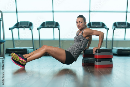 Fotografie, Obraz  Young Woman Doing Triceps Exercise On Stepper