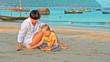 Baby and mother draw in the sand with a stick on the beach with boats in the sea in background