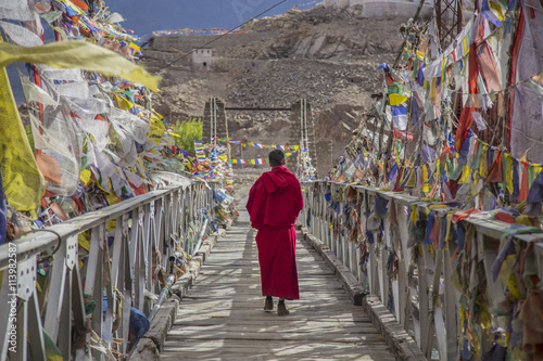 Fotomural A monk walks onthe bridge pathway surrounded by colorful tibetan