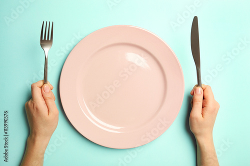 Female hands with cutlery and empty plate on turquoise background Fototapeta
