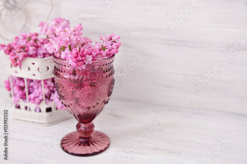 Foto op Canvas Bloemen Bouquets of pink lilac flowers on white wooden background