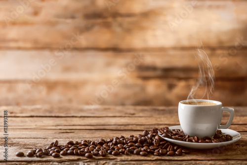 Obraz Cup of coffee with beans on wooden table - fototapety do salonu
