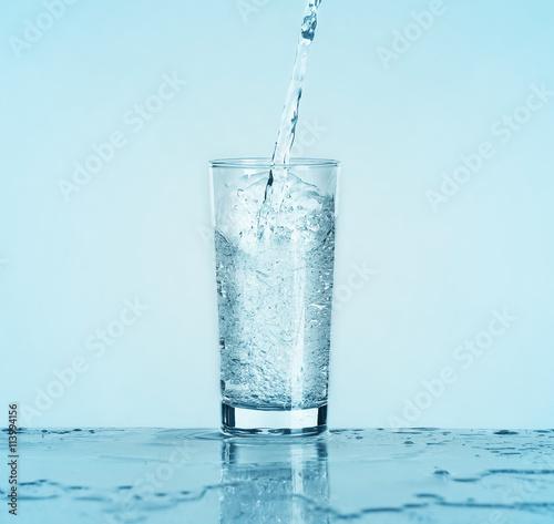 Papiers peints Eau Pouring water into glass on light background