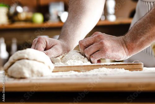 Fotografie, Obraz  Zblízka mužských rukou pekaře hnětení těsta a pečení chleba.