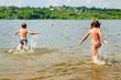 Children running to swim in the river.