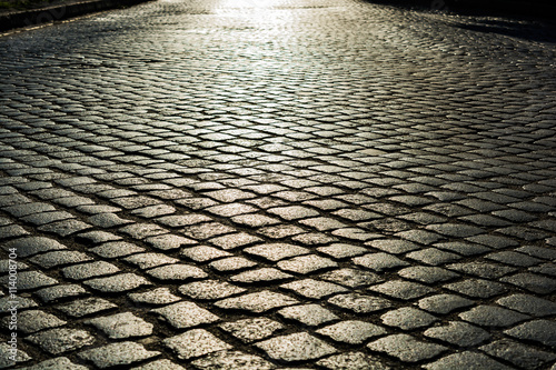 Valokuvatapetti sunlight on cobblestone road. old stone texture