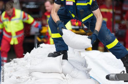 Fotografie, Obraz Helfer transportiert Sandsäcke
