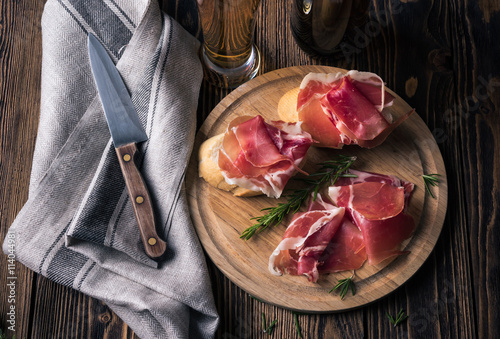 Spanish tapas with jamon on a wooden background