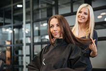 Hairdresser Giving A New Haircut To Female Customer At Parlor