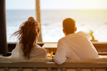 Couple Watching The Sea From The Terrace Of  Their Apartment