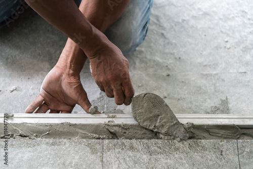 Cuadros en Lienzo Man mason building a screed coat cement on floor