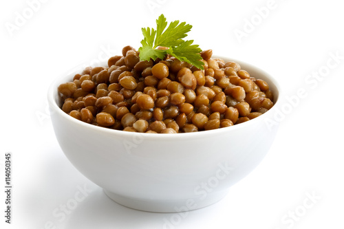 Fotografie, Obraz  White ceramic bowl of brown cooked lentils with parsley isolated