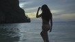 Asian beautiful woman in crochet bikini walking to the sea. Video of sexy girl walking to the sea and shaking hear at the sunset - back view in slow motion.